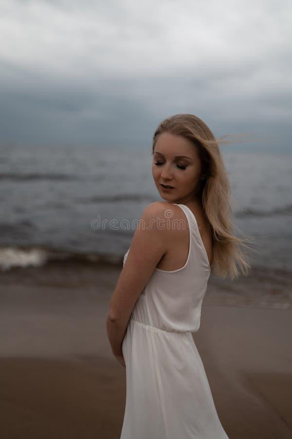 美丽的幼小白肤金发的妇女海滩若虫接近的画象在白色礼服的在有波浪的海附近在一愚钝阴沉期间 库存图片