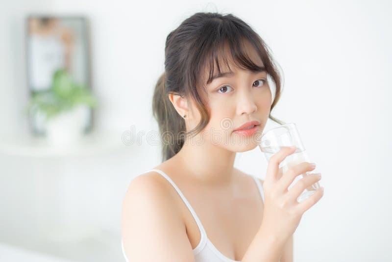美丽的微笑与营养渴和水水杯的画象年轻亚裔妇女白种人矿物与新鲜 免版税图库摄影