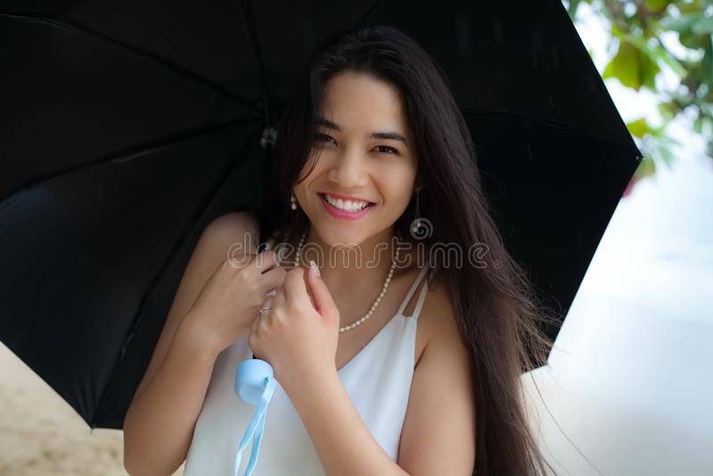 美丽的微笑的两种人种的妇女或青少年的举行的伞在rai 库存照片