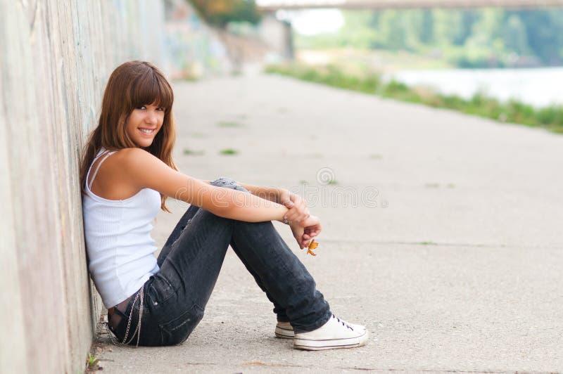 美丽的微笑的十几岁的女孩坐stre 库存照片