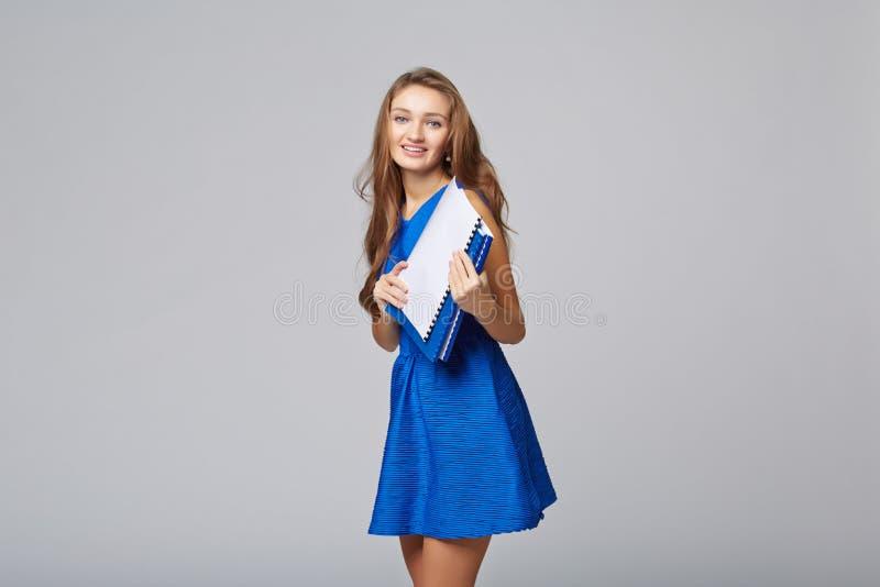 美丽的微笑的女商人,有文件的,在灰色后面 免版税库存图片