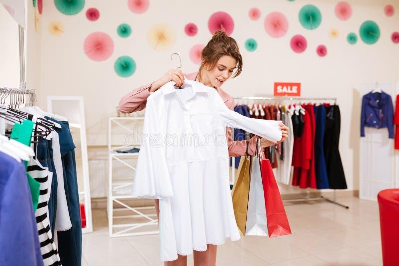 美丽的微笑的女孩去购物和选择白色礼服在衣裳商店 库存图片
