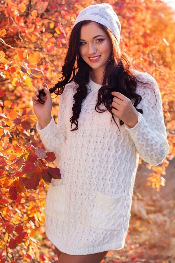 美丽的微笑的女孩在五颜六色的秋天公园 免版税库存照片