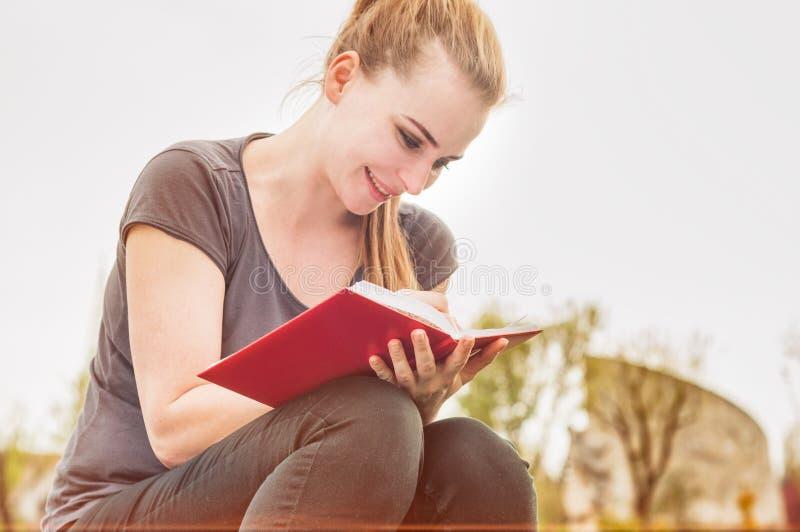 美丽的微笑的女孩在她的日志写在公园 库存照片
