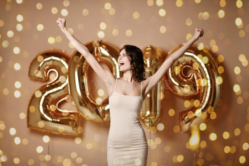 美丽的微笑的女孩画象发光的金黄礼服投掷的五彩纸屑的,获得与金子的乐趣在背景的2019个气球 免版税图库摄影