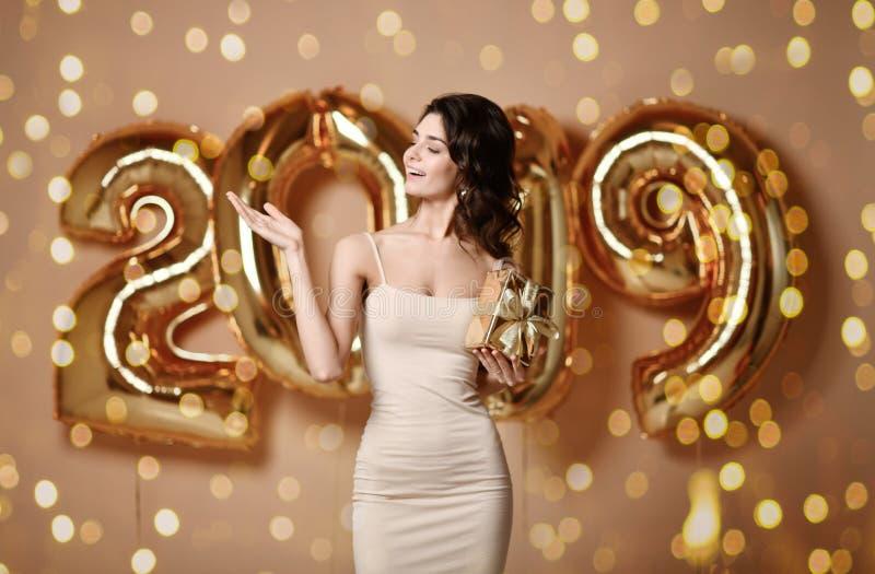 美丽的微笑的女孩画象发光的金黄礼服投掷的五彩纸屑的,获得与金子的乐趣在背景的2019个气球 库存图片