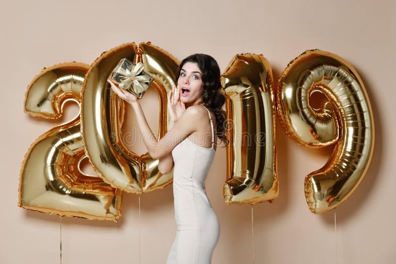 美丽的微笑的女孩画象发光的金黄礼服投掷的五彩纸屑的,获得与金子的乐趣在背景的2019个气球 免版税库存照片