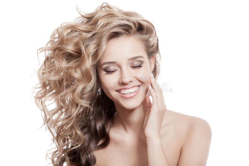 美丽的微笑的妇女。健康长的卷发 库存图片