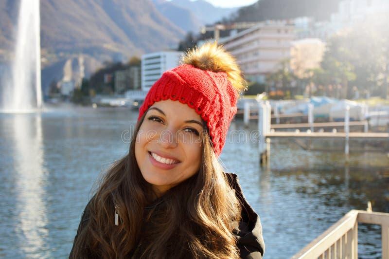 美丽的微笑的妇女与白色牙和冬天穿衣外面与背景和火光轻的阳光的瑞士湖 库存照片
