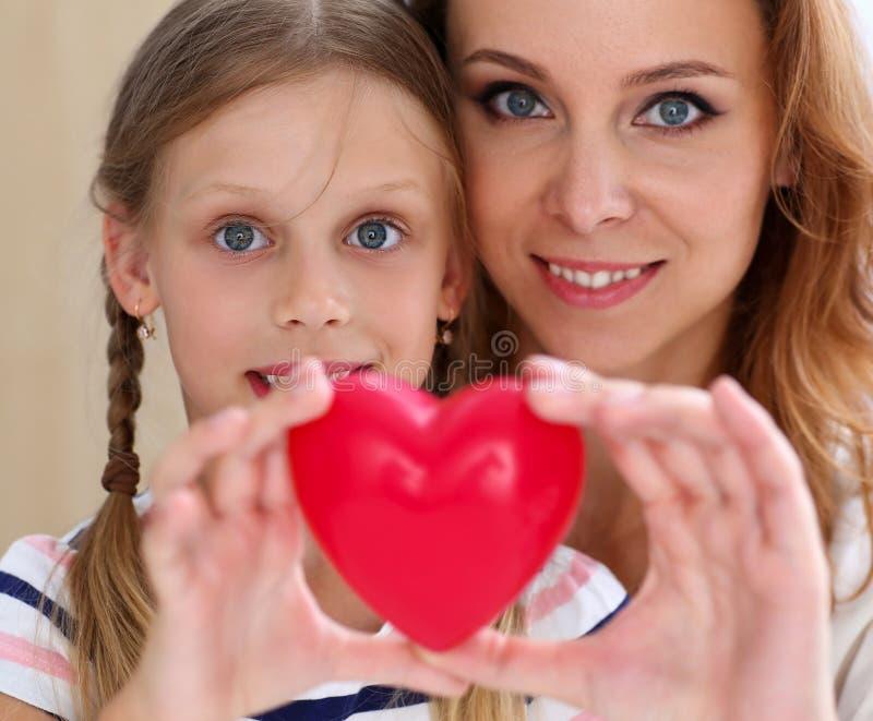 美丽的微笑的妇女和孩子拿着红色玩具心脏 免版税库存照片