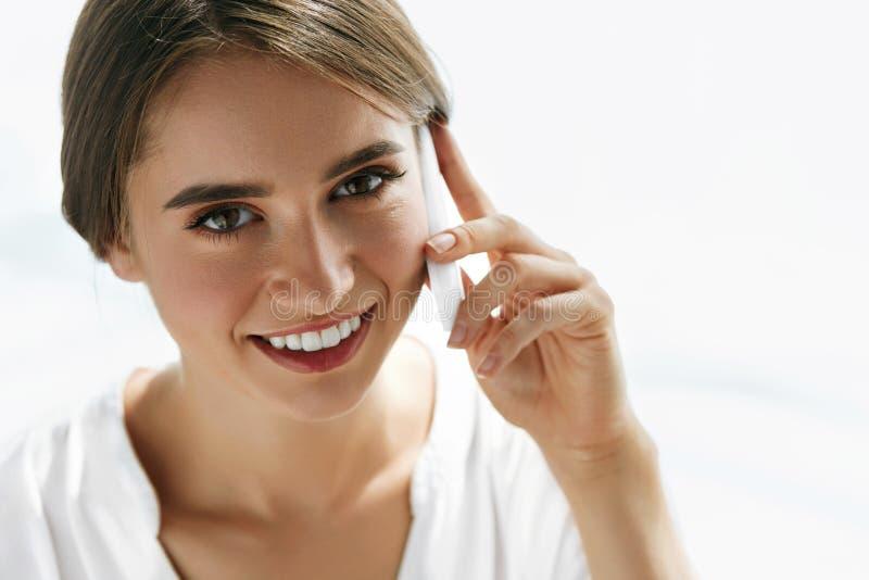 美丽的微笑的妇女在她的手上的拿着手机 免版税库存照片