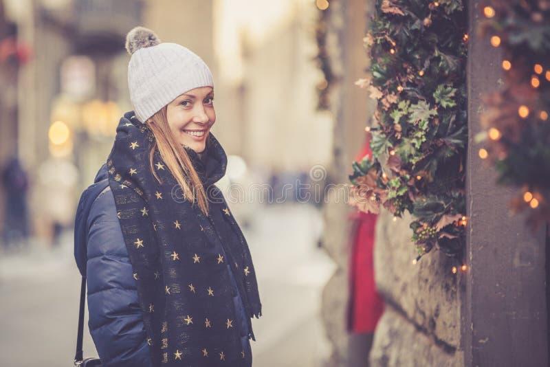 美丽的微笑的妇女在街道的圣诞节冬天期间 免版税库存图片