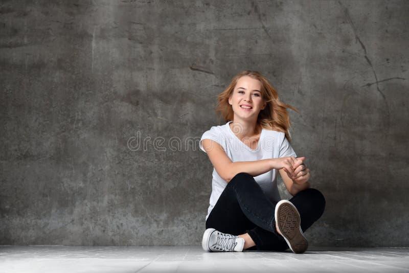 美丽的微笑的妇女坐地板对混凝土墙 免版税库存照片