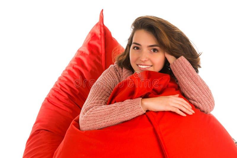 美丽的微笑的妇女坐红色装豆子小布袋沙发椅子室我 免版税图库摄影
