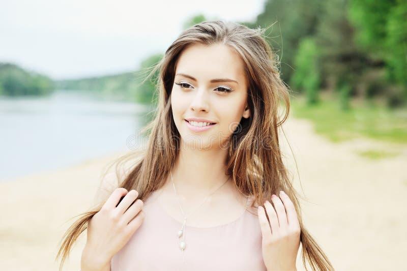 美丽的微笑的妇女室外画象 免版税库存照片