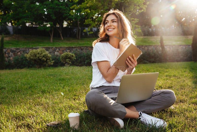 美丽的微笑的妇女画象坐在pa的绿草 免版税库存照片
