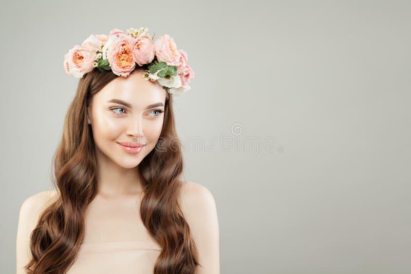 美丽的微笑的妇女画象有清楚的皮肤、长的发光的头发和花的 r 库存照片