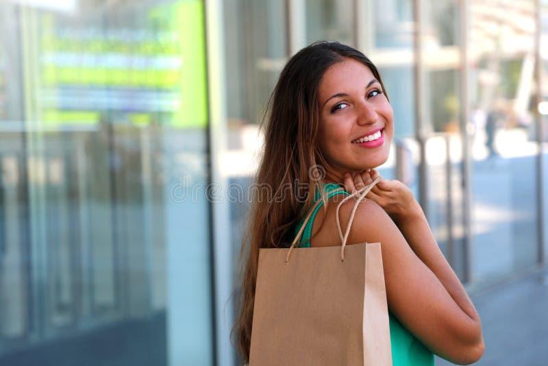 美丽的微笑的妇女画象有购物袋的在墙壁玻璃背景 户外 复制空间 图库摄影