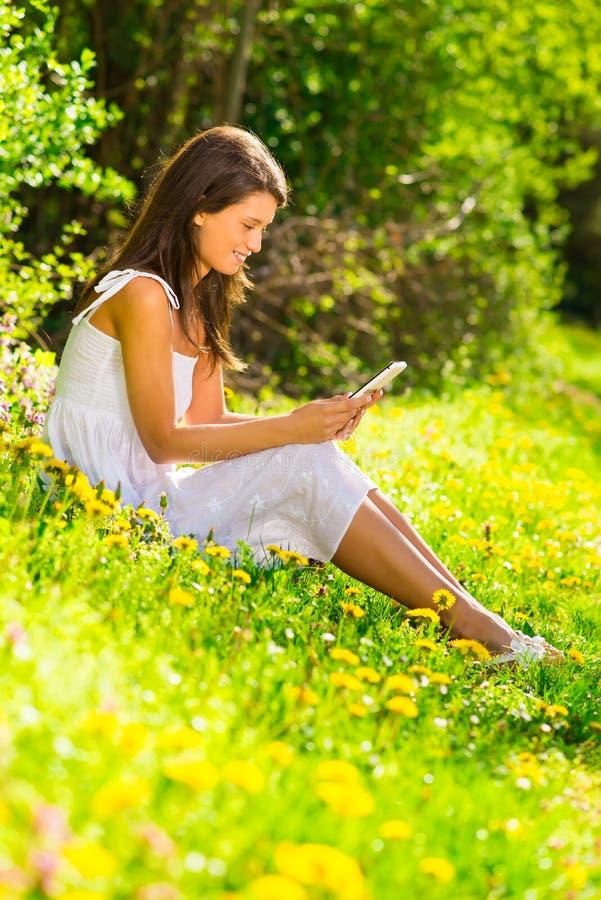 年轻美丽的微笑的妇女画象有片剂个人计算机的 库存图片
