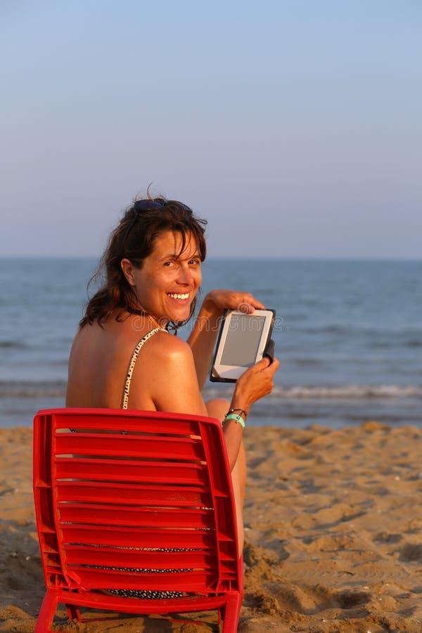 美丽的微笑的妇女读ebook 免版税库存图片