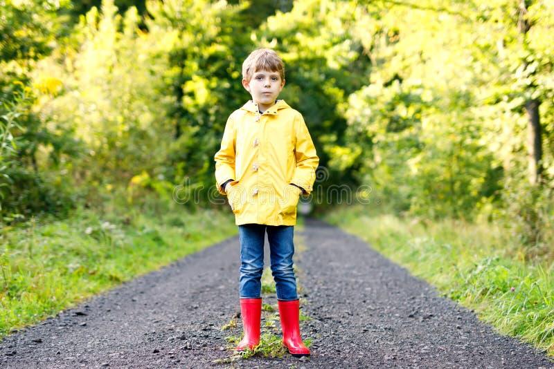美丽的微笑的孩子男孩画象黄色雨夹克和红树胶起动的 反对绿色树背景的愉快的孩子 免版税库存图片