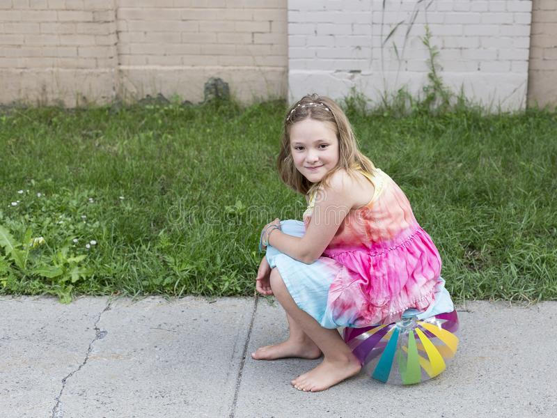 美丽的微笑的小女孩在夏天礼服和赤脚坐在边路的海滩球 免版税库存照片