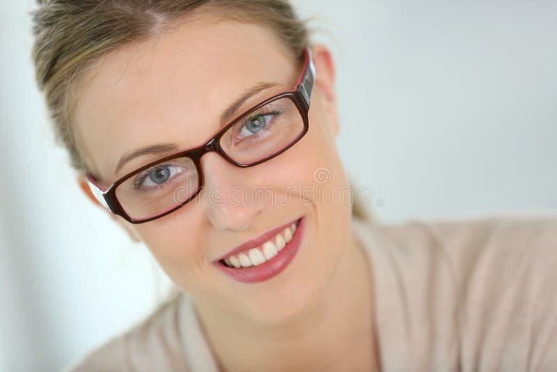 美丽的微笑的少妇佩带的镜片 免版税库存图片