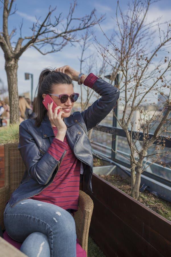 美丽的微笑的少妇坐户外和谈话在手机 免版税库存照片