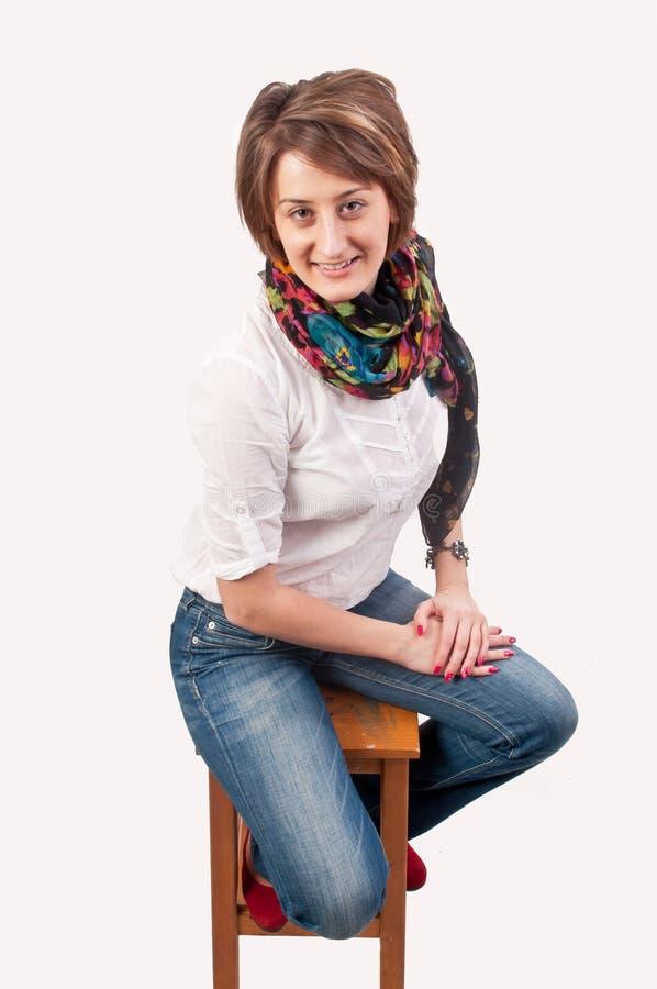 美丽的微笑的少妇坐椅子 免版税库存图片