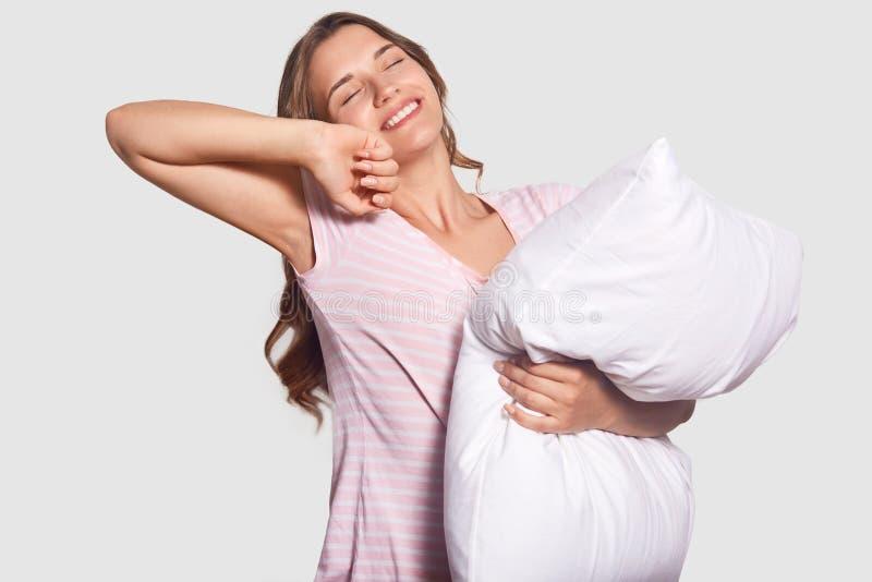美丽的微笑的少妇室内射击在家享受周末,有足够的睡眠,在awakeing以后舒展,拿着枕头,有 图库摄影