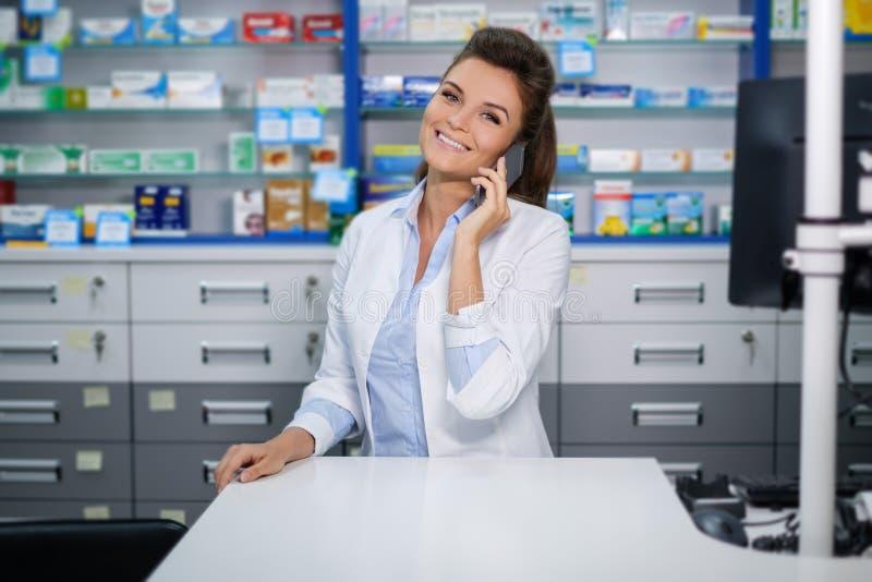 美丽的微笑的少妇药剂师谈话在药房的手机 库存照片