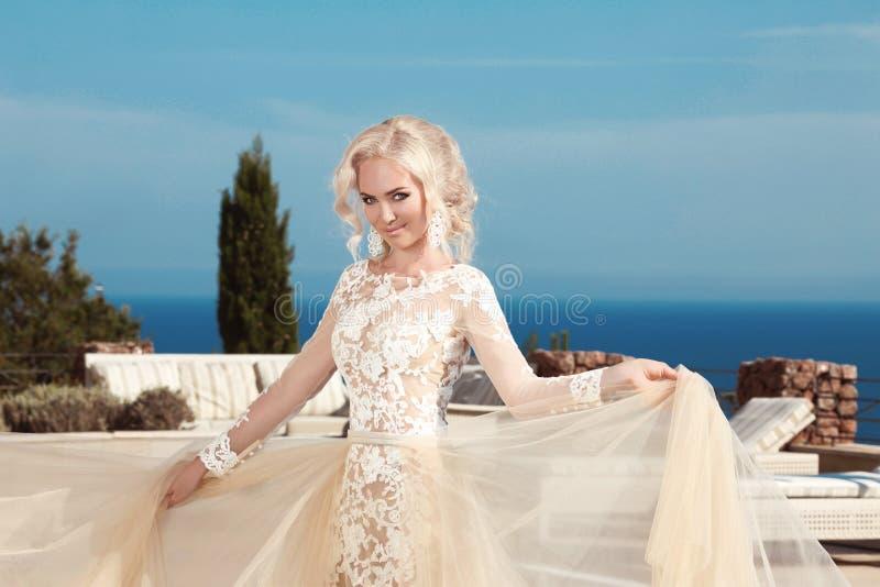 美丽的微笑的新娘在高雅白色婚礼礼服穿戴了 库存照片