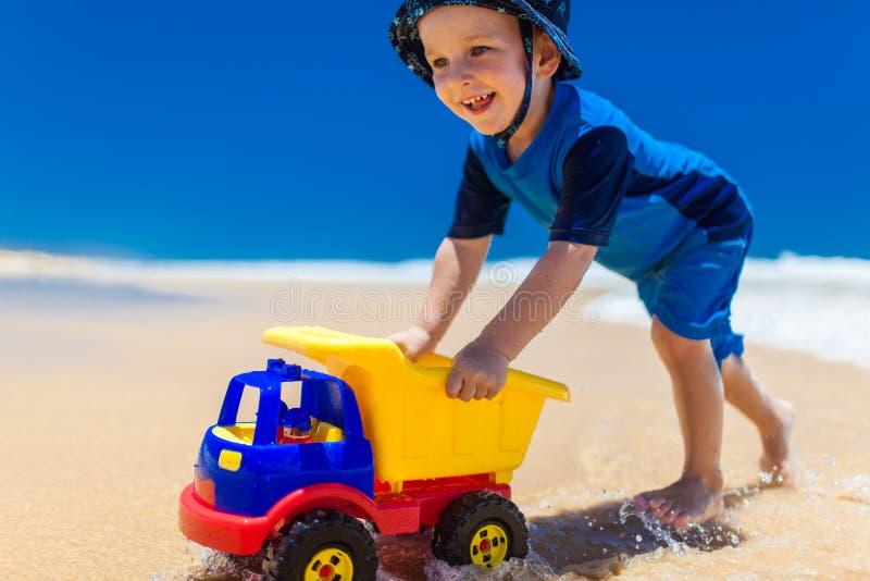 美丽的微笑的男孩在水中的推挤五颜六色的汽车在b 库存图片