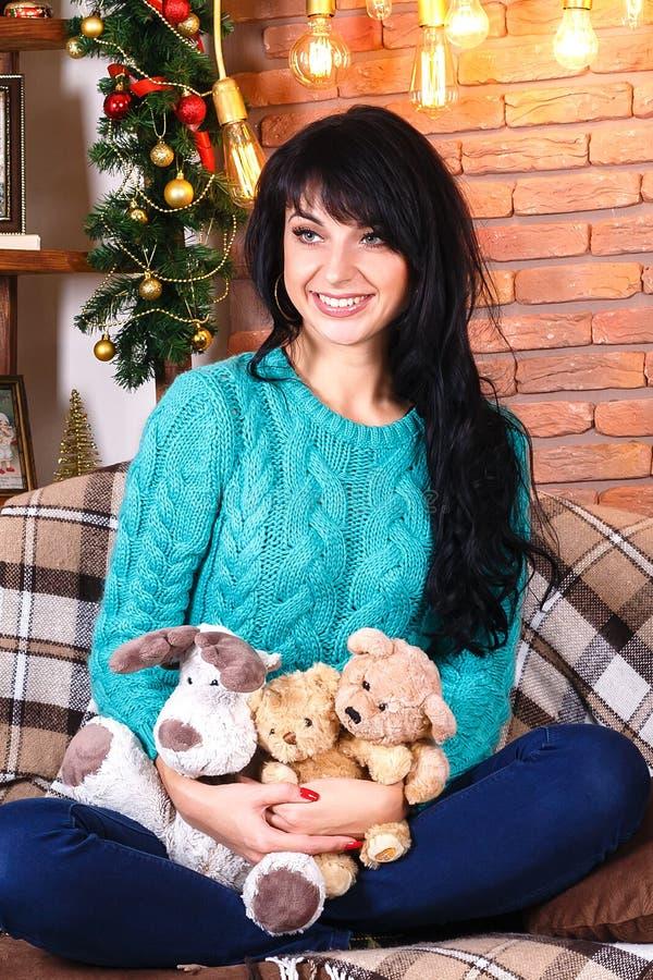 美丽的微笑的西班牙女孩坐在圣诞节12月的沙发 免版税库存图片