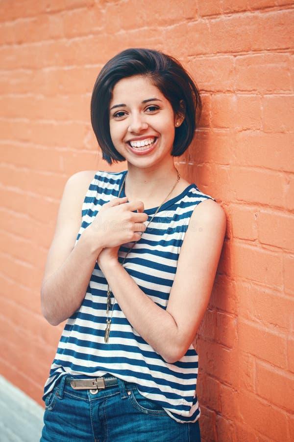 美丽的微笑的年轻行家拉丁西班牙女孩妇女画象有短发突然移动的 库存照片