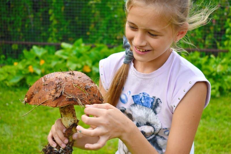 美丽的快乐的女孩用一个大蘑菇在手上 库存图片