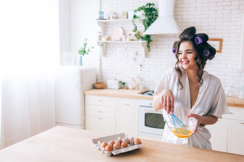 美丽的快乐的好年轻主妇混和的鸡蛋在厨房里 支持和微笑的看 在容器的鸡蛋在桌上 免版税库存图片