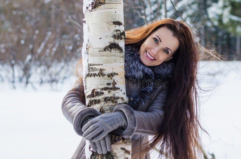 美丽的快乐的妇女在冬天森林里 免版税库存照片