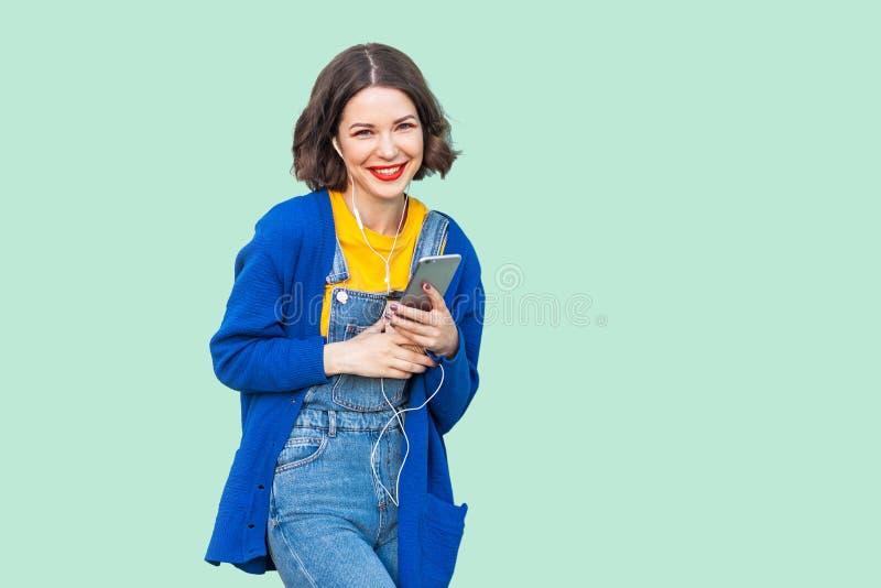 美丽的快乐的年轻妇女画象行家穿戴的在站立牛仔布的总体,拿着电话和听的喜爱 免版税图库摄影