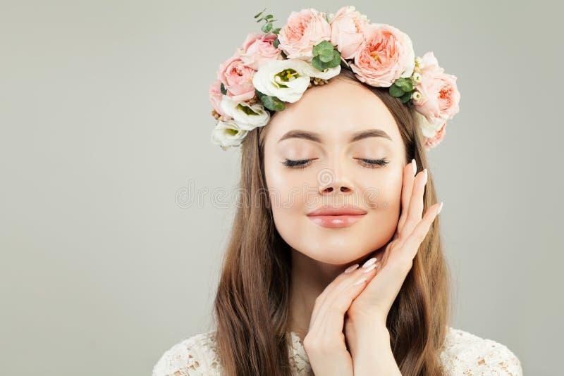 美丽的快乐的年轻式样妇女画象 与清楚的皮肤、自然构成和桃红色玫瑰花的完善的女性面孔 免版税库存照片