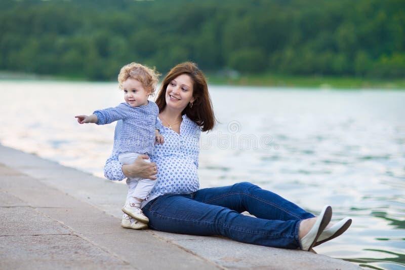 美丽的怀孕的母亲和她的小女儿在河支持 库存图片