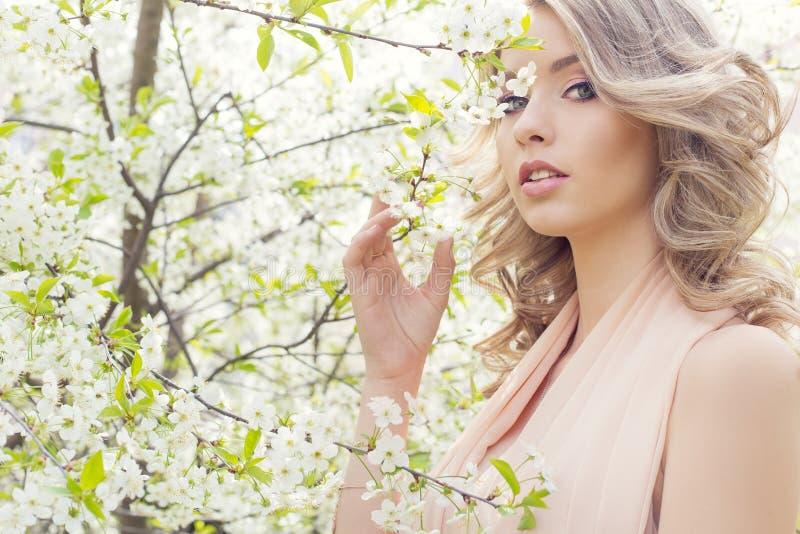 美丽的性感的典雅的甜蓝眼睛的白肤金发的女孩在樱花附近的庭院里在一晴朗的明亮的天 免版税库存图片