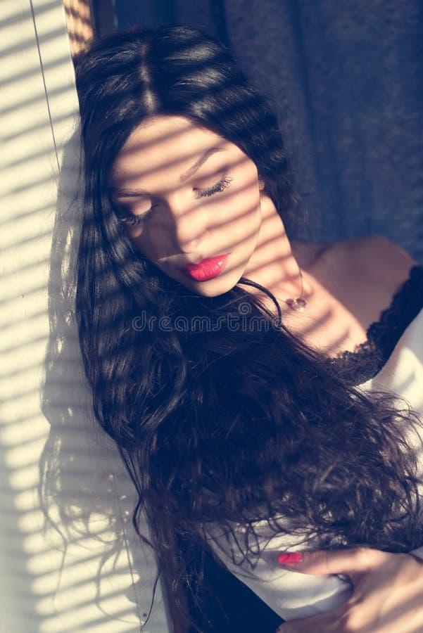 美丽的性感的女孩深色的少妇眼睛特写镜头画象关闭与从太阳被点燃的窗帘的阴影 免版税库存照片
