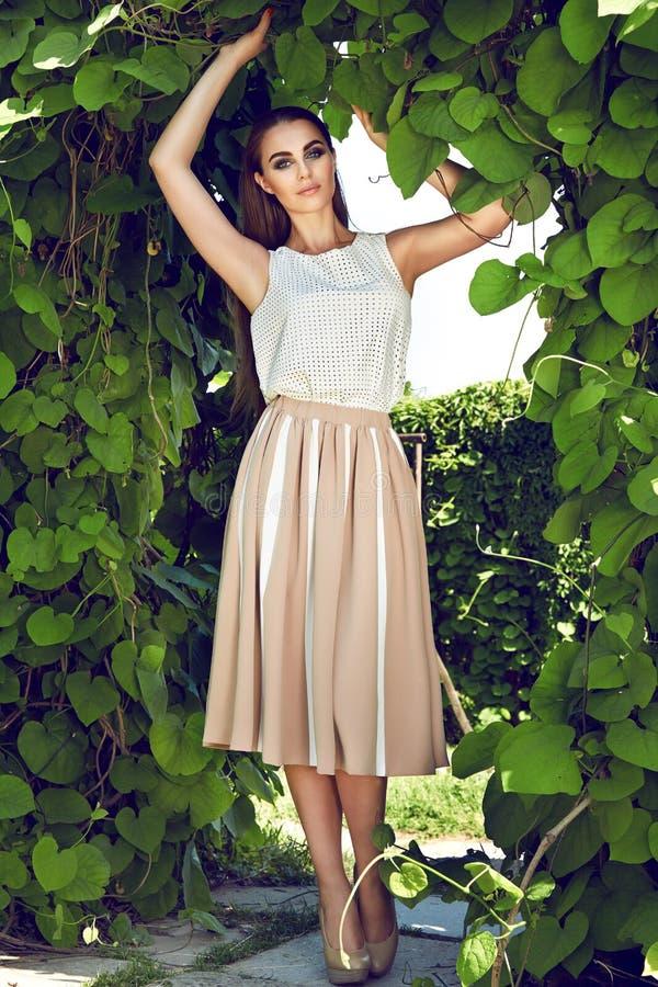 美丽的性感的妇女佩带的礼服步行公园太阳亮光构成 库存照片