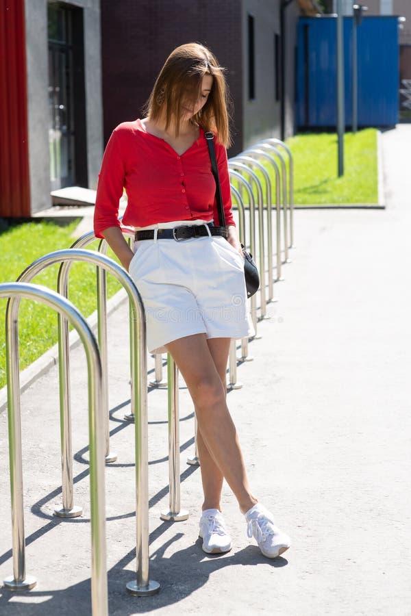 美丽的性感的妇女深色的长发穿戴丁香丝绸女衬衫和白色棉花短裤鞋子,时装模特儿企业样式衣裳 免版税图库摄影