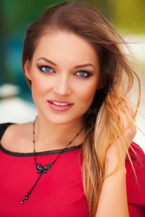 美丽的性感的妇女画象有红色礼服和金发摆在的室外 塑造女孩 免版税库存图片