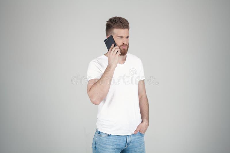 美丽的性感的有胡子的人画象  他在外形和谈话站立在电话 他在白色前面站立 库存图片