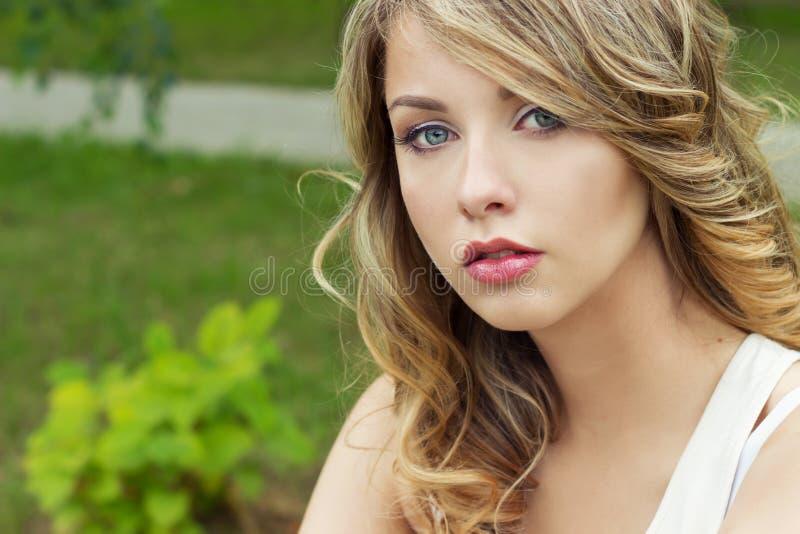 美丽的性感的白肤金发的女孩画象在有大肥满嘴唇的一个公园 免版税库存照片