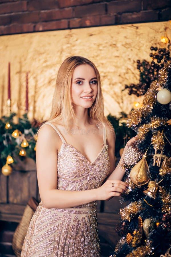 美丽的性感的白肤金发的女服一件金黄礼服并且装饰圣诞树 假日、庆祝和人们 库存图片
