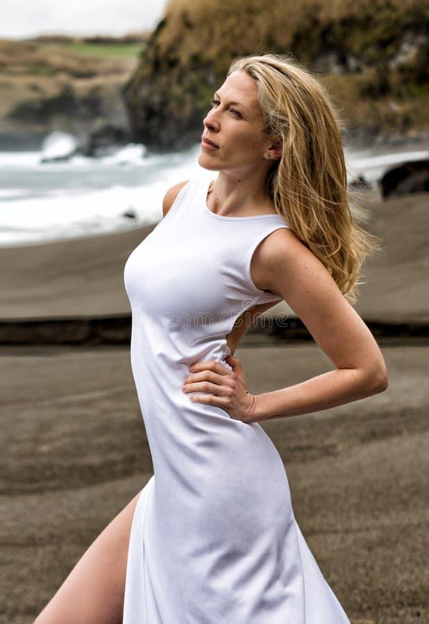 美丽的性感的白肤金发的妇女在白色长的礼服摆在一黑沙滩在亚速尔 免版税库存照片